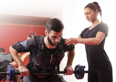 Beautiful female personal trainer assisting young man exercising on ems
